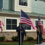 veterans outside a home with american flags for an open house ceremony