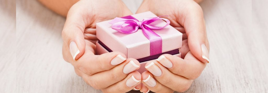 woman offering gift representing donations to charities year round