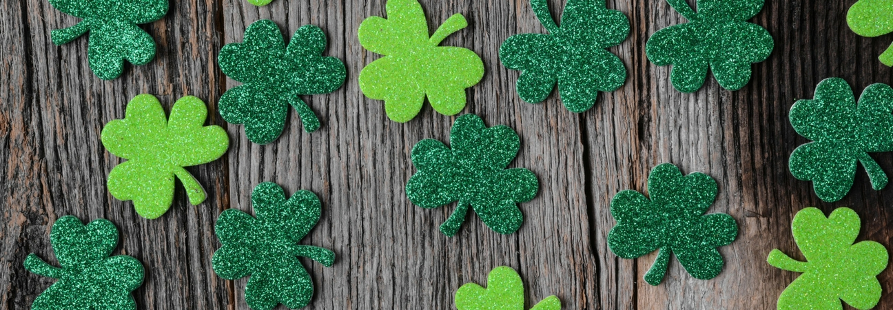 four leaf clovers on a wooden background to supplement a blog about raleigh nonprofit fundraiser